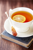 Cup of Tea with Lemon and brown Sugar Stick  on a old Book. Symbolic image. Rustic wooden background.  - 227641721