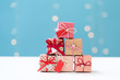 Small Christmas gift boxes on a shiny light blue background