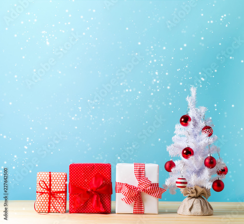 Foto Murales White Christmas tree and gift boxes in a snowy day