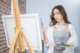 Portrait of happy asian beautiful sexy woman paint in her art studio. Young asian girl holding her paintbrush. Artist workshop class education concept - 227653986