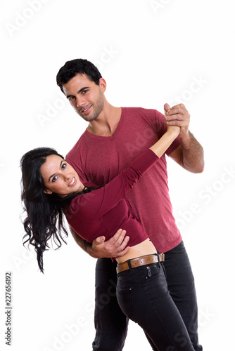 Studio shot of young happy couple smiling while dancing together