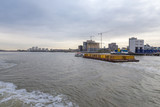 Barge pulling a load of containers downriver at Woolwich, London