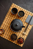 Asian green tea set on bamboo mat with dried green tea. Black vintage iron pot and cups. Asian tea concept