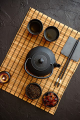 Asian green tea set on bamboo mat with dried green tea. Black vintage iron pot and cups. Asian tea concept