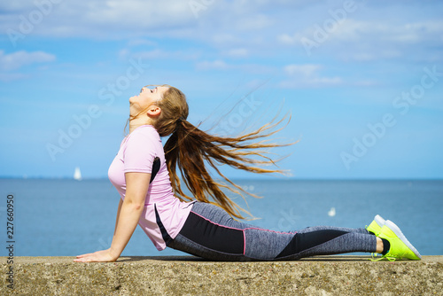 Woman doing yoga next to sea