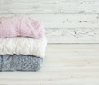 Stack of woolen clothes on wooden white table close up