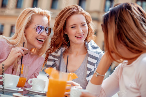 Poster Group of young female friends sitting in cafe