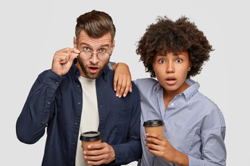 Picture of astonished mixed race woman and man stare with surprised epressions at camera, cannot believe own eyes, drink coffee, pose against white background together. Interracial couple indoor