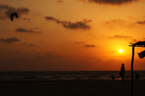 Kitesurfer and girl silhouette on sunset background, India, Goa