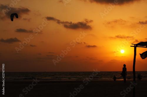 Foto Murales Kitesurfer and girl silhouette on sunset background, India, Goa
