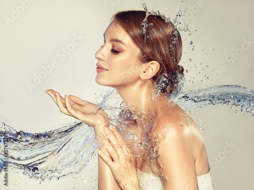Beautiful spa woman with water splashes. Moisturizing facial skin, beauty and care. - 227679788