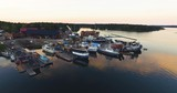 Aerial flyover an old colorful boatyard outside the swedish east coast with beautiful sunset reflections in the water. - 227699534