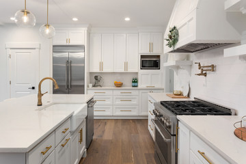 Beautiful kitchen detail in new luxury home. Features island, pendant lights, hardwood floors, and stainless steel appliances