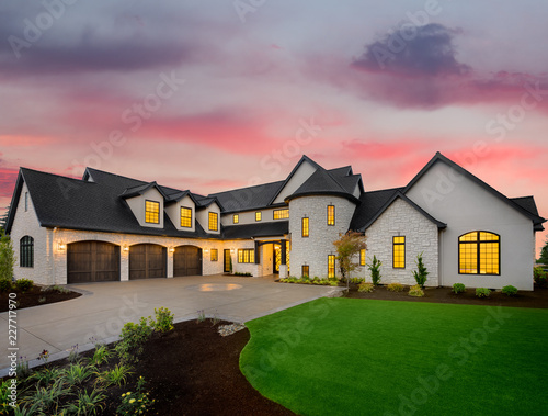 Stunning Luxury Home Exterior at Sunset with Colorful Sky. This Mansion has Three Garages, Turret Style Tower, and Two Floors