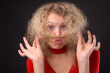 Young beautiful woman with blond curly hair against gray backgro - 227729338