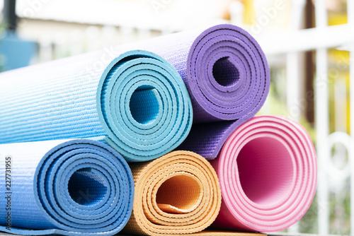 bliska kolorowe maty do jogi na stole, sport i zdrowe pojęcie