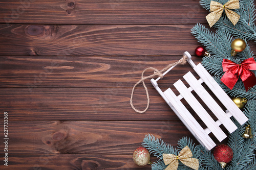 Christmas toy sledge with fir-tree branch on a brown background