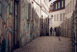 lovely couple walking in narrow street with graffiti