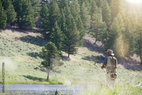 Foto Murales Fisherman flyfishing in river of Montana state