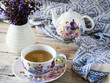 Home interior decor, bouquet of mauve flowers in a vase and blue fabric on rustic wooden table with set of teapot.