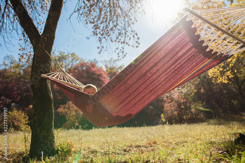 Little boy resting lying in hammock at golden autumn day