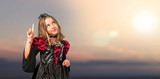 Blonde child dressed as a vampire for halloween holidays counting number one sign at outdoor with sunset - 227758746