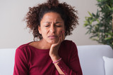Woman feeling toothache and massaging gums