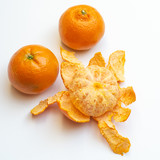 Two mandarins and one peeled on a white background