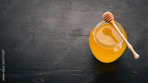 Honey in a jar on a black wooden background. Free space for text. Top view. © Yaruniv-Studio