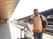 Joyful caring hindu father and his little son enjoying travelling by train while standing on the railway station