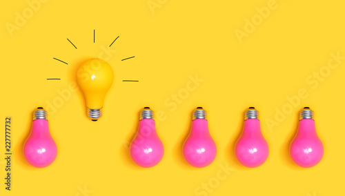 One outstanding idea concept with yellow and pink light bulbs