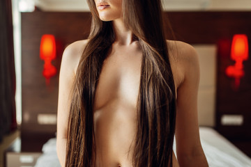 Brunette woman with long hair and bare breasts