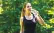Young woman with a water bottle on a bright summer day in the forest