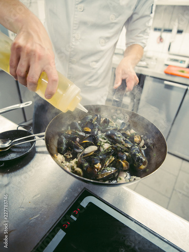 Poster Close-up of chef's hands cooking on basin mussels. Served on the table. National food.