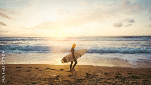 Silhouette of beautiful surfer on the beach at sunset - 227784586
