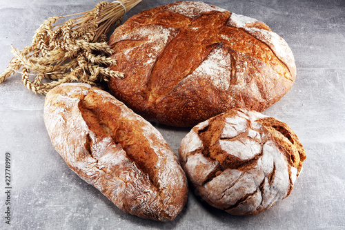 Different kinds of bread and bread rolls on board from above. Kitchen or bakery - 227789919