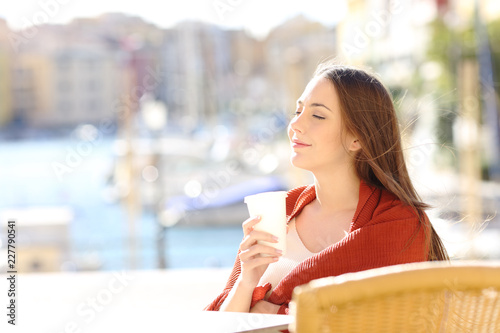 Woman relaxing holding a drink in a coffee shop