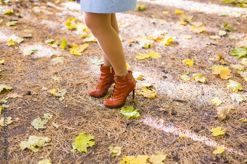 Autumn fashion. Female legs in stylish fashionable shoes boots, outdoor golden leaves