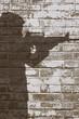Mann zielt mit einem Gewehr. Schatten auf einer Wand.
