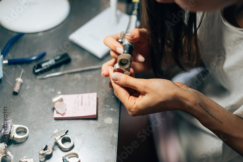 The girl works on a jewelry in the workshop © teksomolika