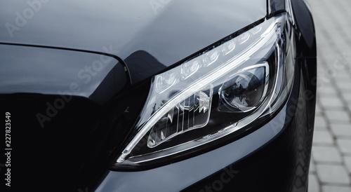 Closeup headlight luxury sedan car lighting road. - 227823549