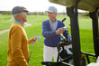 Two cheerful aged buddies in pullovers and caps discussing the forthcoming game of golf while choosing clubs