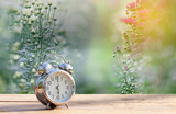 Vintage alarm clock on wooden table with green nature bokeh background.with copy space for text.