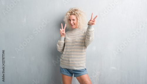 Leinwandbild Motiv Young blonde woman with curly hair over grunge grey background smiling looking to the camera showing fingers doing victory sign. Number two.