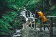 woman walking to waterfall in yellow raincoat - 227881734