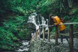 woman walking to waterfall in yellow raincoat