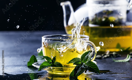 Foto Murales Hot chinese green tea with mint, with splash pouring from the kettle into the cup, steam rises, dark background, selective focus