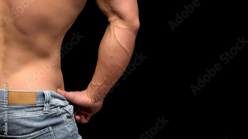 bez koszulki mężczyzna w dżinsach na biodrach położył dłoń na talii. Zamknąć widok