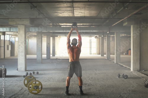 Wall mural Athlete is engaged in crossfit in brutal gym
