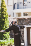 man in robe is standing in courtyard on summer morning - 227898122